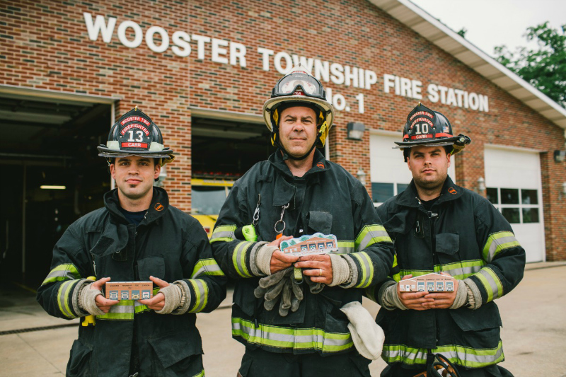 Wooster Township firefighters holding Cat's Meow replicas of their fire station.