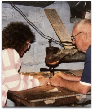 Faline with her grandfather, Rudy Mullet, cutting on the bandsaw he built from scratch.