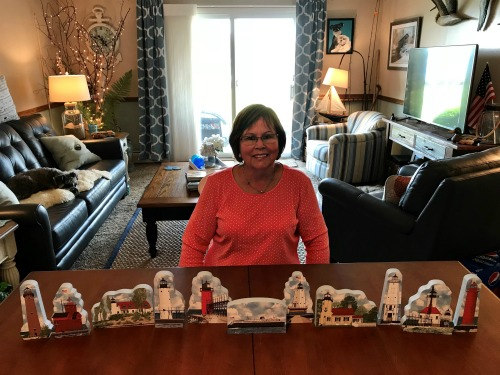 Sandy Lea with her newly unpacked Cat's Meow Michigan lighthouses in her Michigan vacation home.