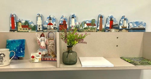 Sandy's display of the Cat's Meow Village Michigan lighthouses on top of her work desk at  her workplace!