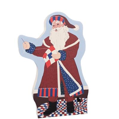 Red, White and Blue Santa is stitching up a patriotic 9 patch quilt block. Handcrafted in Wooster, Ohio by The Cat's Meow Village.
