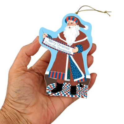 "Santa will stitch your holiday message on his quilt banner for a very personal ornament. Handcrafted in 3/4"" thick wood by The Cat's Meow Village in Wooster, Ohio."