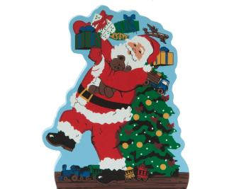 Handcrafted wooden shelf sitter of Santa caught delivering presents created by The Cat's Meow Village