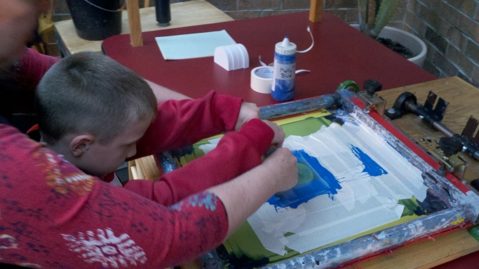 Boy Scout learns to screen print at the Cat's Meow Village.