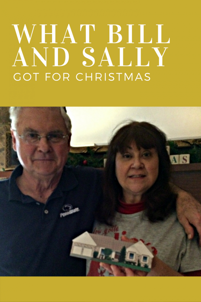 Bill and Sally holding the best Christmas present ever...a Cat's Meow personalized replica of their home.