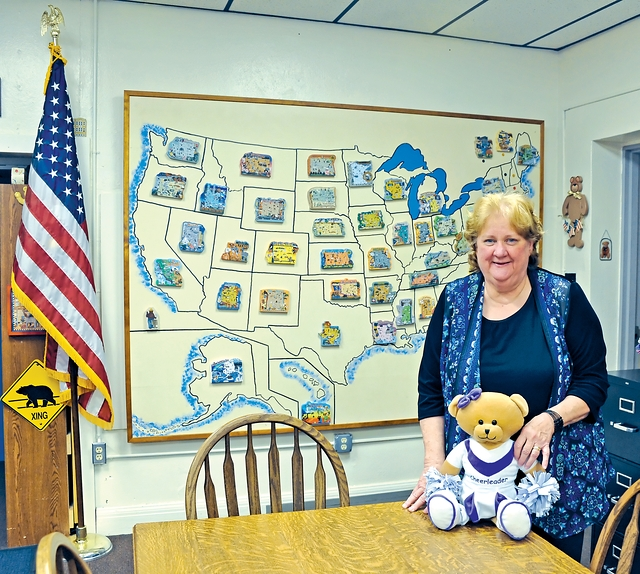 Marcia Hosfeld, librarian at Shreve Elementary School with Cat's Meow Village United States Map hanging in library.