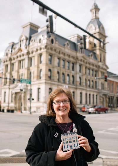 Cat's Meow owner, Faline Jones, showing off her handcrafted wooden replica of the Wayne County Courthouse