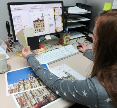 Designer, Ashlea, doing a final color check and putting finishing touches on our Cat's Meow Wayne County Courthouse design