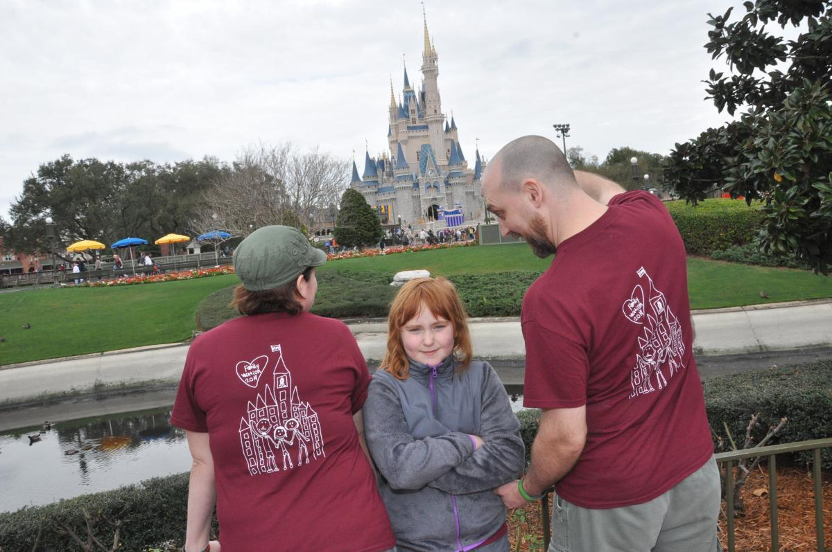 The Ciha family modeling the backs of their Disney shirts.