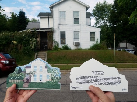 Holding up the Cat's Meow heirloom replica of the Wyatt home in front of the actual home.